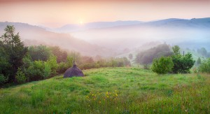 Haymaking in a Carpathian village. Colorful summer sunrise in the foggy mountain.