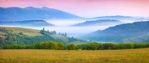 Panorama of the sunny summer morning in the foggy Carpathian mountains. Borzhava ridge, Transcarpathian, Ukraine, Europe.
